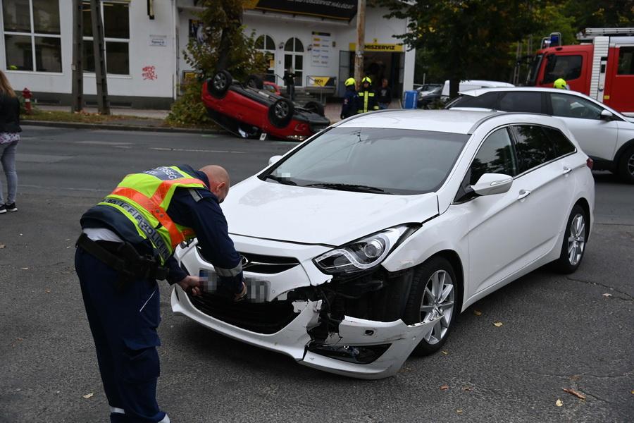 Budapest, 2021. szeptember 29. Rendőr helyszínel sérült személyautónál, a háttérben felborult gépjármű, miután két személygépkocsi összeütközött a XIV. kerületi Vezér utca és Fogarasi út kereszteződésében 2021. szeptember 29-én. A balesetben egy ember megsérült. MTI/Mihádák Zoltán