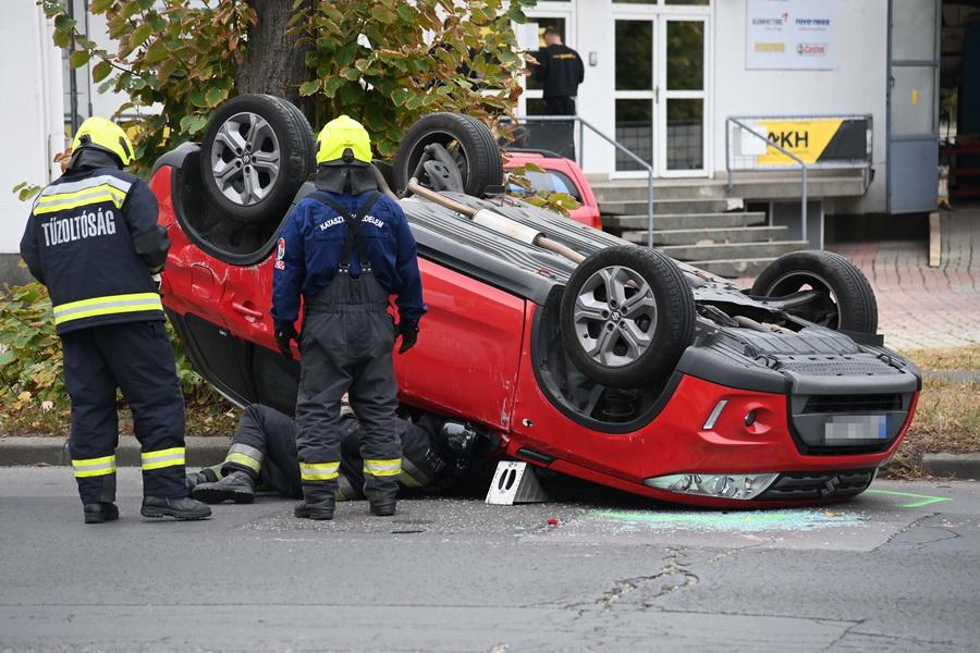 Budapest, 2021. szeptember 29. Tűzoltók felborult személyautónál, miután két személygépkocsi összeütközött a XIV. kerületi Vezér utca és Fogarasi út kereszteződésében 2021. szeptember 29-én. A balesetben egy ember megsérült. MTI/Mihádák Zoltán